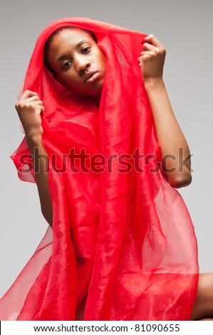 Slender young black woman in a red cloak