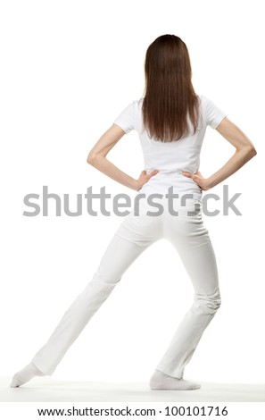 Slender young woman doing sport exercises; rear view on white background