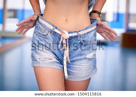 Slender young woman in big jeans with a centimeter tape.