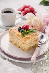 Slice cake of puff pastry with mint, raspberry and blueberry on plate, cup of coffee, peony. Delicate and airy composition, vertical format.