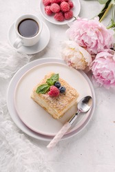 Slice cake of puff pastry with mint, raspberry and blueberry on plate, cup of coffee, peony. Delicate and airy composition, vertical format, top view