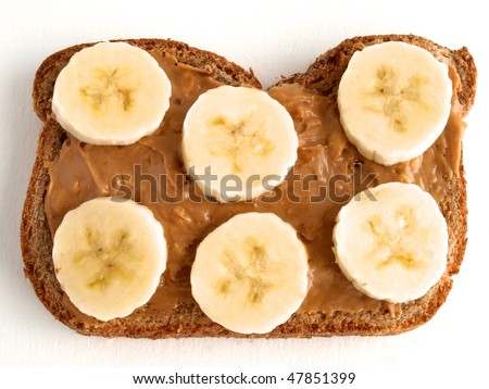 Slice fresh banana on crunchy peanut butter coated single slice of dark wheat bread. Peanut butter and banana sandwich.