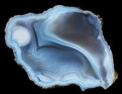 Slice geode of natural blue-white agate with smooth concentric lines texture on black background
