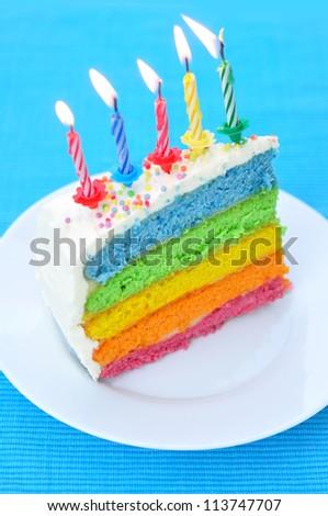 Slice of a layer rainbow cake