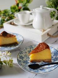 slice of baked cheese cake, a sweet dessert consisting of two layers. The main, and thickest layer, consist of cream cheese, eggs, and sugar. And a bottom layer, consists of a crust or crushed cookies