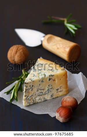 Slice of blue cheese and nuts on an old board.