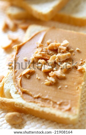 Slice of bread with peanut butter and nuts. Peanut butter is excellent addition for sandwiches and desserts.