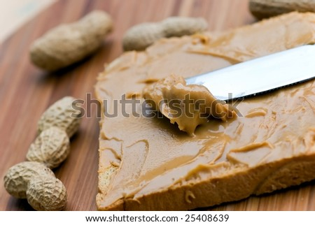 Slice of bread with peanut butter spread on wooden background