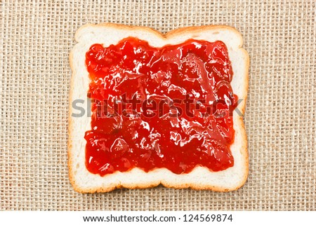slice of bread with strawberry jam on sacking background
