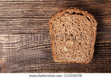 Slice of brown bread on a wooden table
