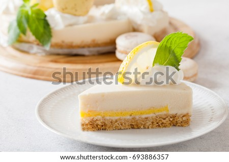Slice of cheesecake with lemon filling decorated with macarons and flowers. Healthy organic summer dessert pie.
