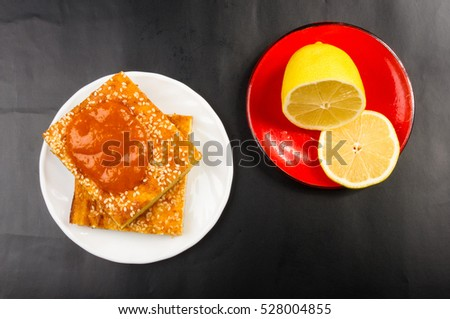 Slice of cheesecake with sesame seeds, apricot jam and lemon slices on a black background #528004855