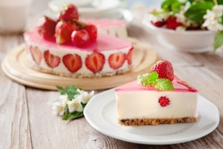 Slice of cheesecake with strawberry filling decorated with cherry jelly and fresh berries. Healthy organic summer dessert pie