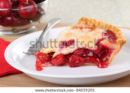 Slice of cherry pie on a plate with cherries in background