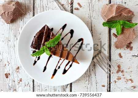Slice of chocolate cheesecake on plate, above view over a rustic white wood background