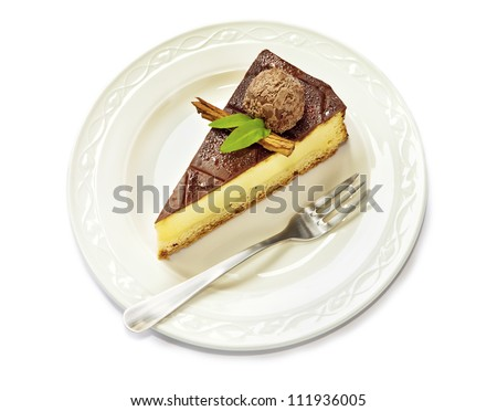 Slice of chocolate covered cheesecake with truffle served on plate.  Closeup, isolated on white background