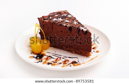 Slice of chocolate cream cake on a plate with cherry.