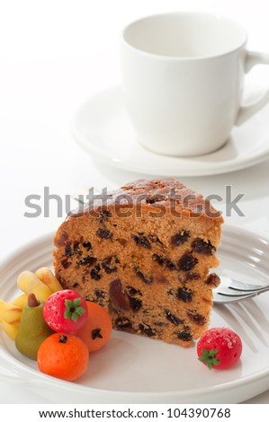 Slice of Dundee cake with marzipan fruits on a white background