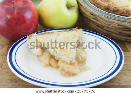Slice of dutch apple pie with apples and pie behind