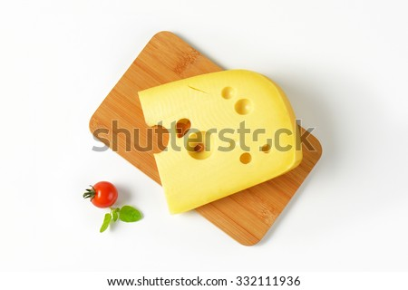 slice of fresh cheese on wooden cutting board