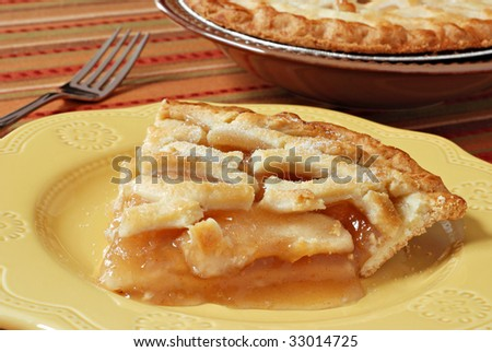 Slice of freshly baked apple pie on decorative plate.  Colorful tablecloth and whole pie in background.  Macro with shallow dof.