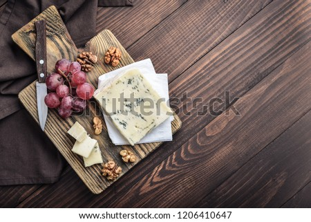 Slice of Gorgonzola cheese on cutting board served with grape and nuts top view