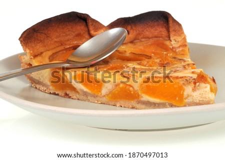 Slice of homemade apricot pie in a plate with a spoon close-up on white background | Part de tarte aux abricots maison dans une assiette avec une cuillère en gros plan sur fond blanc Photo stock ©