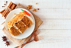 Slice of homemade carrot cake with cream cheese frosting. Above view over a rustic white wood background.