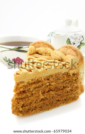 Slice of honey and nut cream cake  and cup of tea on white background