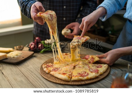 Slice of hot pepperoni pizza, large cheese lunch or dinner with cheese. Delicious tasty fast food italian traditional on wooden board table classic in side view. People hands taking slices of pizza.