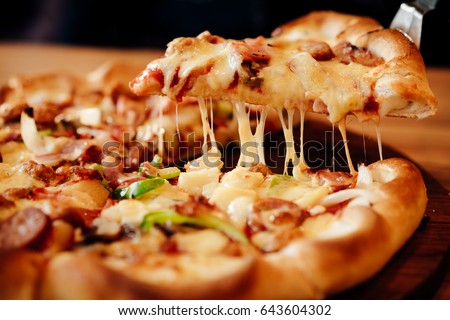 Slice of hot pizza large cheese lunch or dinner crust seafood meat topping sauce. with bell pepper vegetables delicious tasty fast food italian traditional on wooden board table classic in side view .