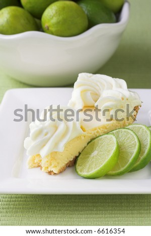 Slice of key lime pie with limes