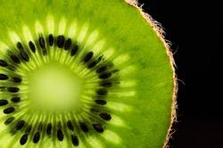 slice of kiwi fruit close-up on black background. horizontal. space for text