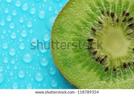 Slice of kiwi with drop on blue background