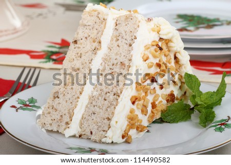 Slice of layer cake with white icing on a Christmas plate