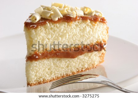 """Slice of layered vanilla or lemon cake, stuffed with """"Dulce de leche"""" (milk jam) is Argentina's traditional desert. It's made over many hours by caramelizing sugar in milk.,"""