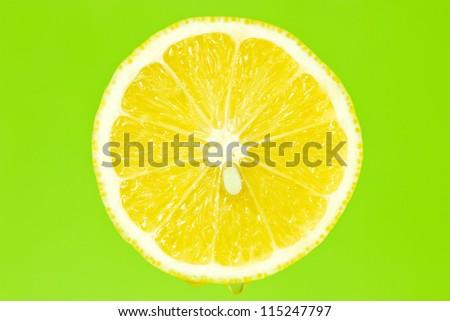 Slice of lemon fruit isolated on green background