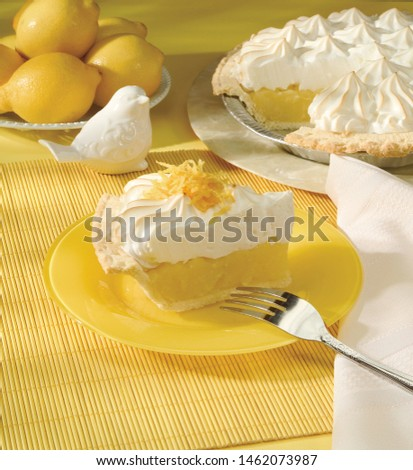Slice of lemon meringue pie with whole pie and whole lemons in background  #1462073987