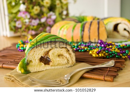 Slice of Mardi Gras King Cake - Slice of traditional New Orleans style King Cake to celebrate Mardi Gras. It's decorated in the traditional Mardi Gras colors of purple, gold, and green with beads.