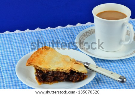 Slice of mincemeat pie with flaky golden brown crust and cup of coffee on very country style setting with blue gingham place mat and old fashioned fork.