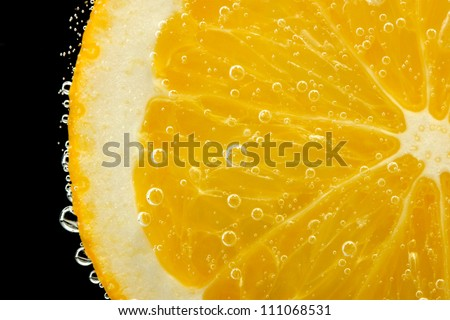 slice of orange in the water with bubbles, on black background