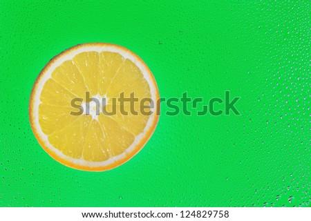 Slice of orange on green drop background