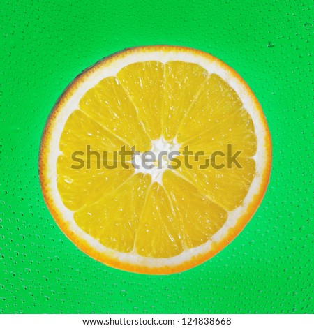 Slice of orange on green drop background