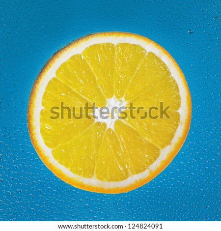 Slice of orange with drop on blue square background