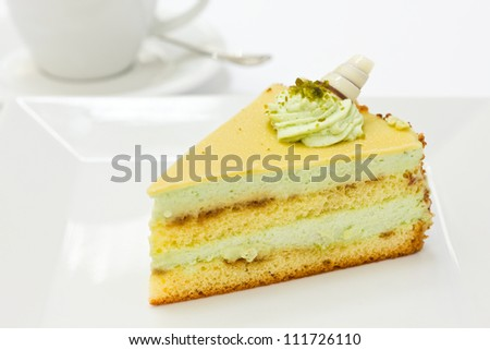 Slice of pistachio sponge cake with fondant icing on a white plate with a cup of coffee slightly out of focus in the background