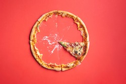 Slice of pizza ham on red cardboard background, top view. Pizza leftovers and crumbs. Last piece of pizza.