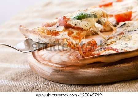 Slice of pizza with ham, vegetables and cheese taken from wooden pizza peel with steel pizza slice server