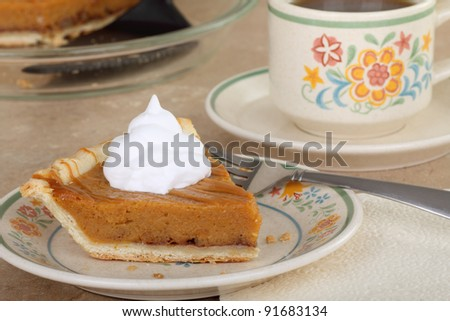 Slice of pumpkin pie with whipped cream and a cup of coffee