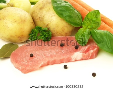 Slice of raw pork with potatoes, carrots and herbs