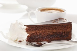 Slice of Sacher cake in plate with coffee